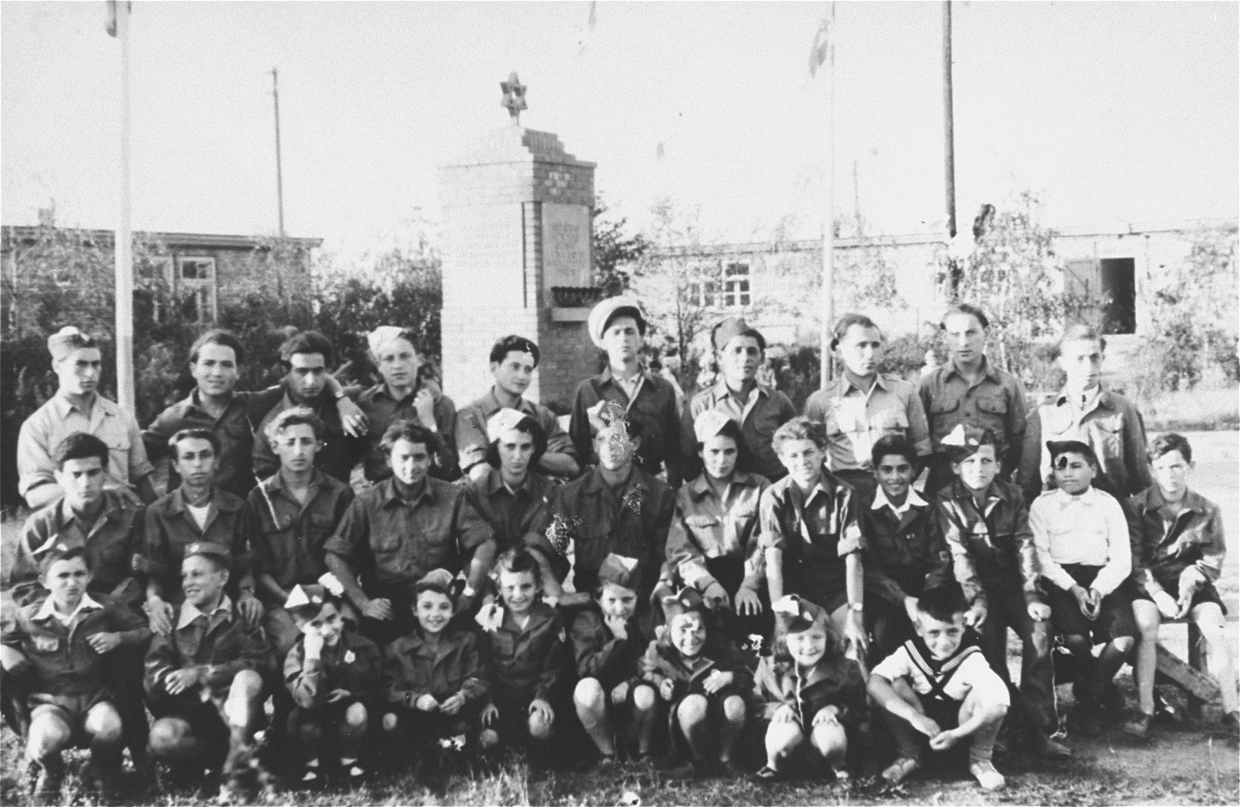 Group portrait of members of a Zionist youth organization posing in front of a monument in the Zeilsheim displaced persons camp.