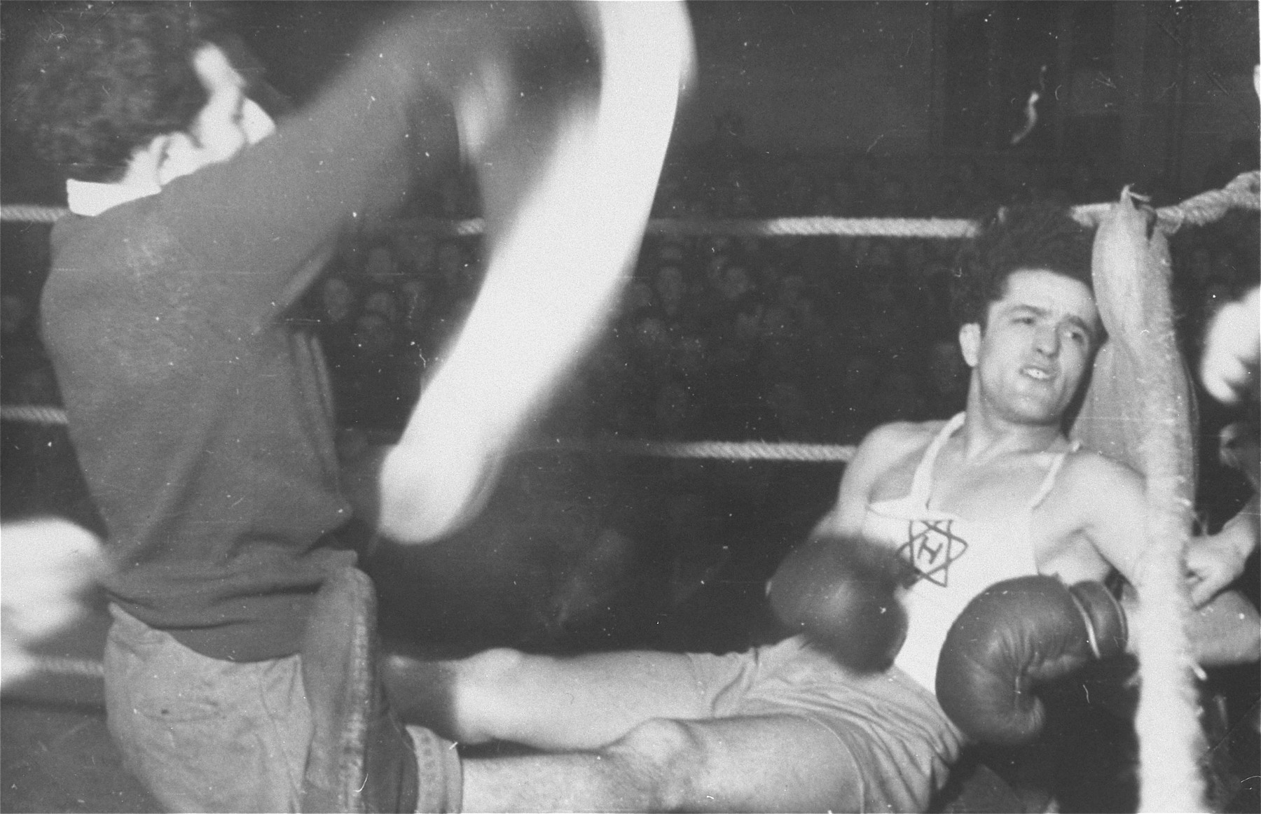 A boxer rests by the side of the ring during a match at the Zeilsheim displaced persons' camp.