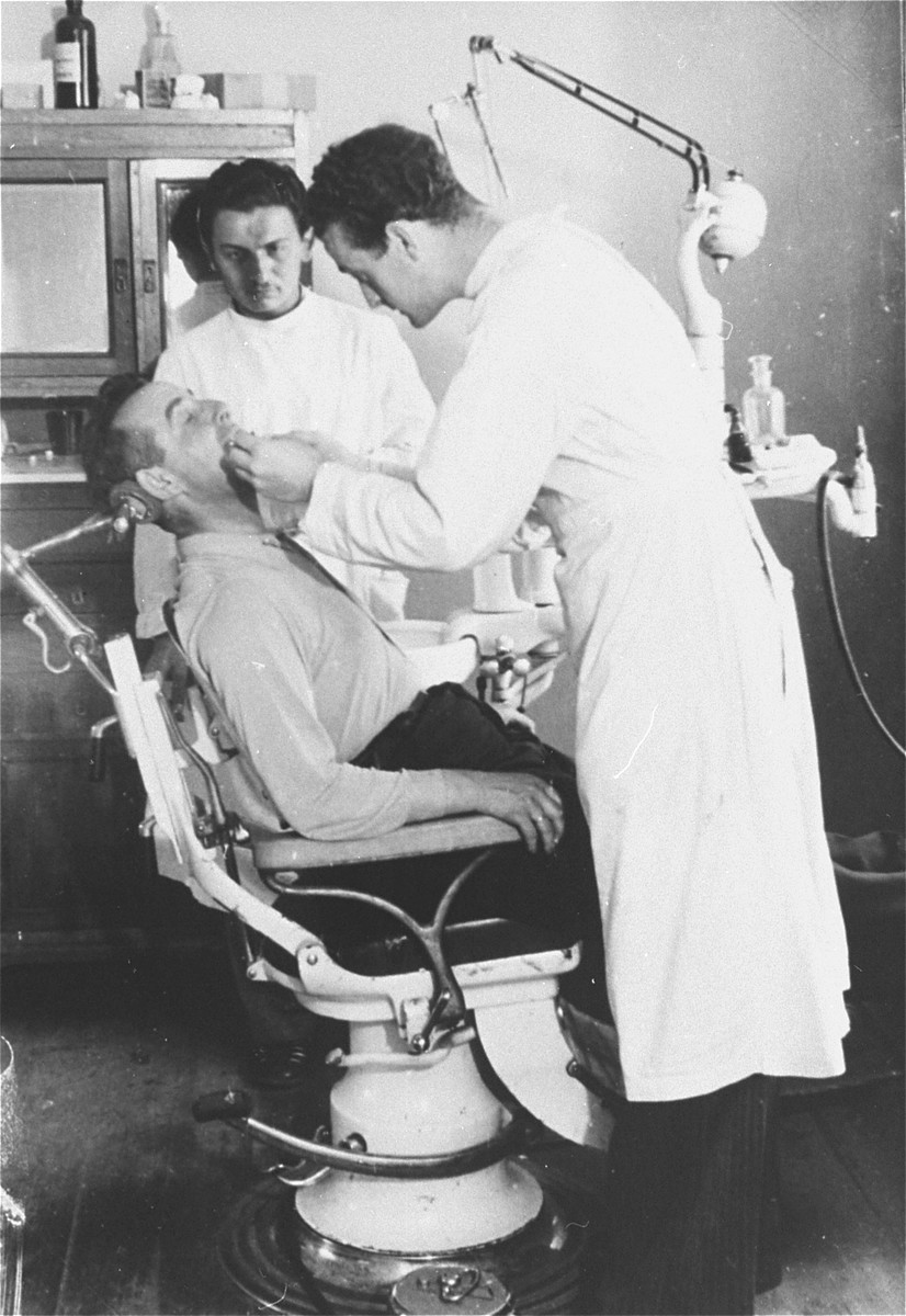 A dentist treats a camp resident in his office in the Zeilsheim displaced persons' camp.