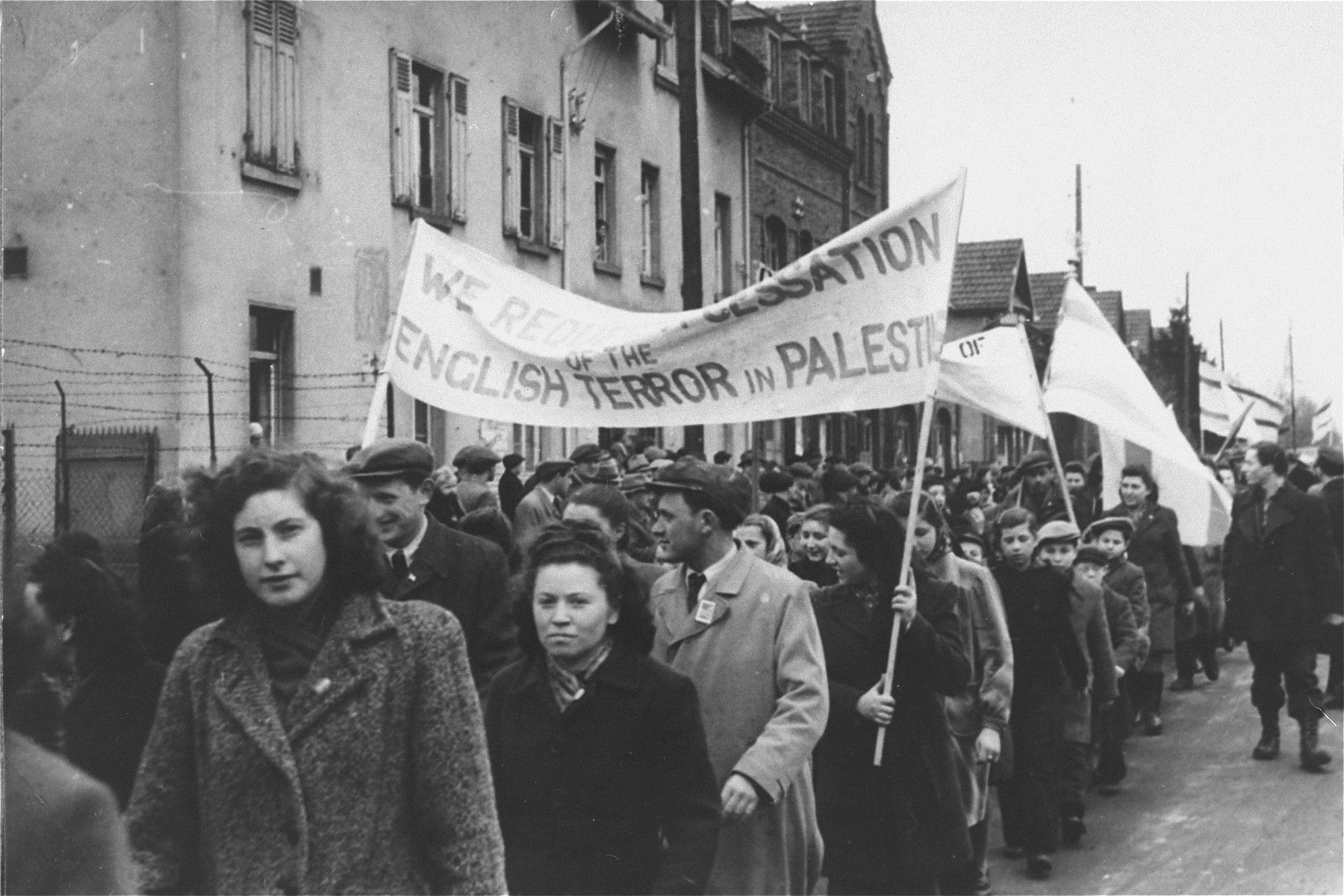 Men and women in the Zeilsheim displaced persons' camp carrying banners march in a demonstration for free immigration to Palestine.