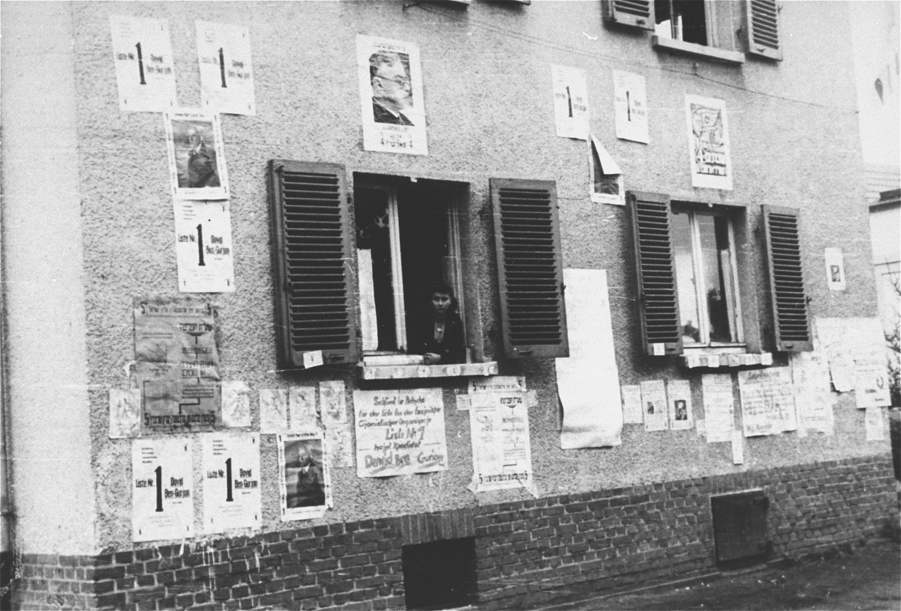 Election campaign posters are plastered on the walls of buildings in the Zeilsheim displaced persons' camp.