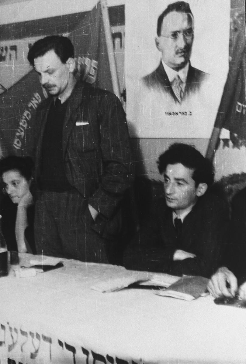 Yitzhak Zuckerman delivers a speech at a Zionist meeting in Zeilsheim.  A portrait of the socialist Zionist theorist Ber Borochov hangs behind the speaker.