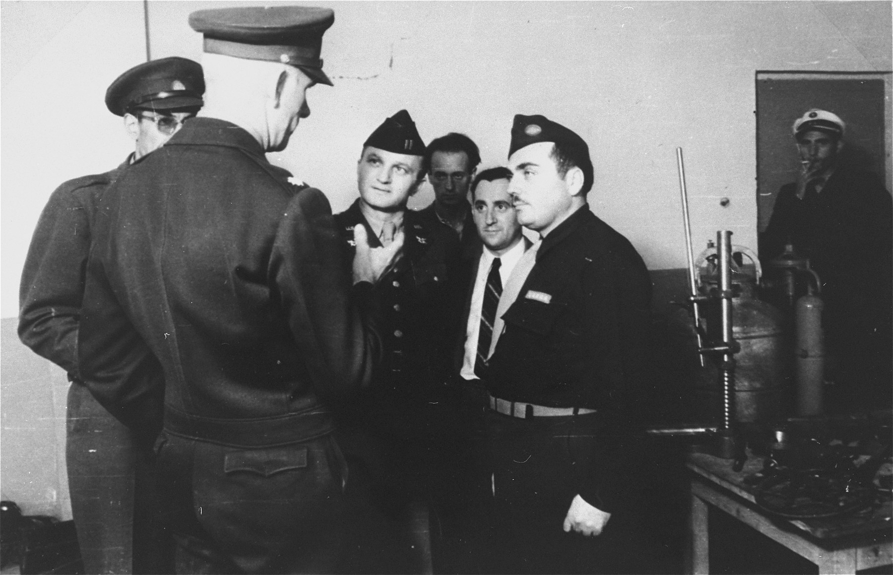 Members of the US army visit the Zeilsheim displaced persons camp.  Among those pictured are Sidney Flatow, UNRRA director of the Zeilsheim displaced persons camp, on the right and David Greenbaum, seen in the doorway smoking.   Mr. Flatow later became the executive director of the American Federation of Polish Jews.