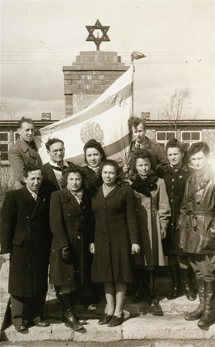 Zionist youth stand with a Zionist flag in front of a memorial in the Zeilsheim displaced persons' camp.  Pictured here in the back row, second from the left is Sheyne-Bela Berk (Propis), and Luba Autoputsky, in the front row, first on the right.  Lula is first cousin of Jona Wigardsky.