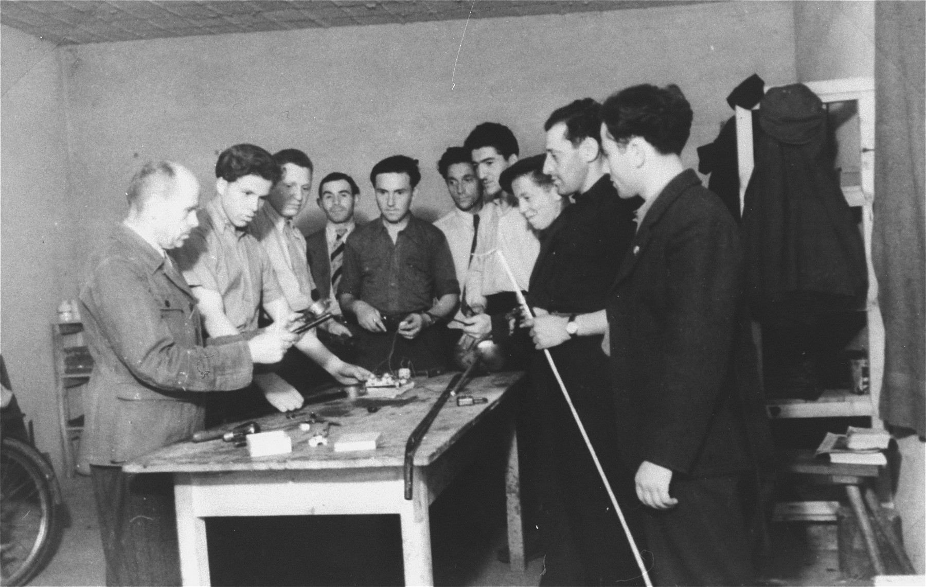 Men gather around a table for a tools demonstration in an ORT sponsored vocational school in the Zeilsheim displaced persons' camp.  Pictured among the men in the background is Jana Wisgardisky.
