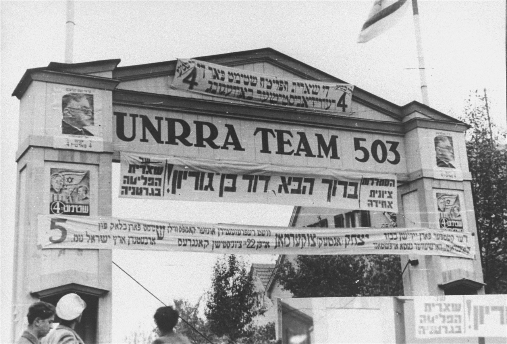 "Election campaign banners posted on the gate of the Zeilsheim displaced persons' camp.    The banner at the top reads:  ""The Surviving Remnant votes for List # 4, the Revisionist Movement.""  The banner in the middle reads:  ""The United Zionist Labor Union of the Surviving Remnant in Germany welcomes David Ben Gurion.""  The banner at the bottom reads:  ""The fighter for Jewish honor, fighter of the Warsaw Ghetto Uprising,Yitzhak (Antek) Zuckerman will represent us at the 22nd Zionist Congress.  Vote for List #5."""