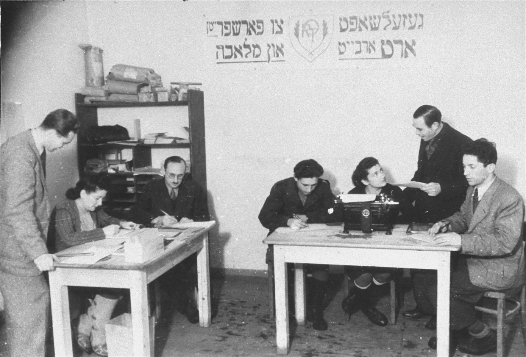 ORT office in the camp. The man pictured on the right speaking to the secretary is Jana Wisgardisky.