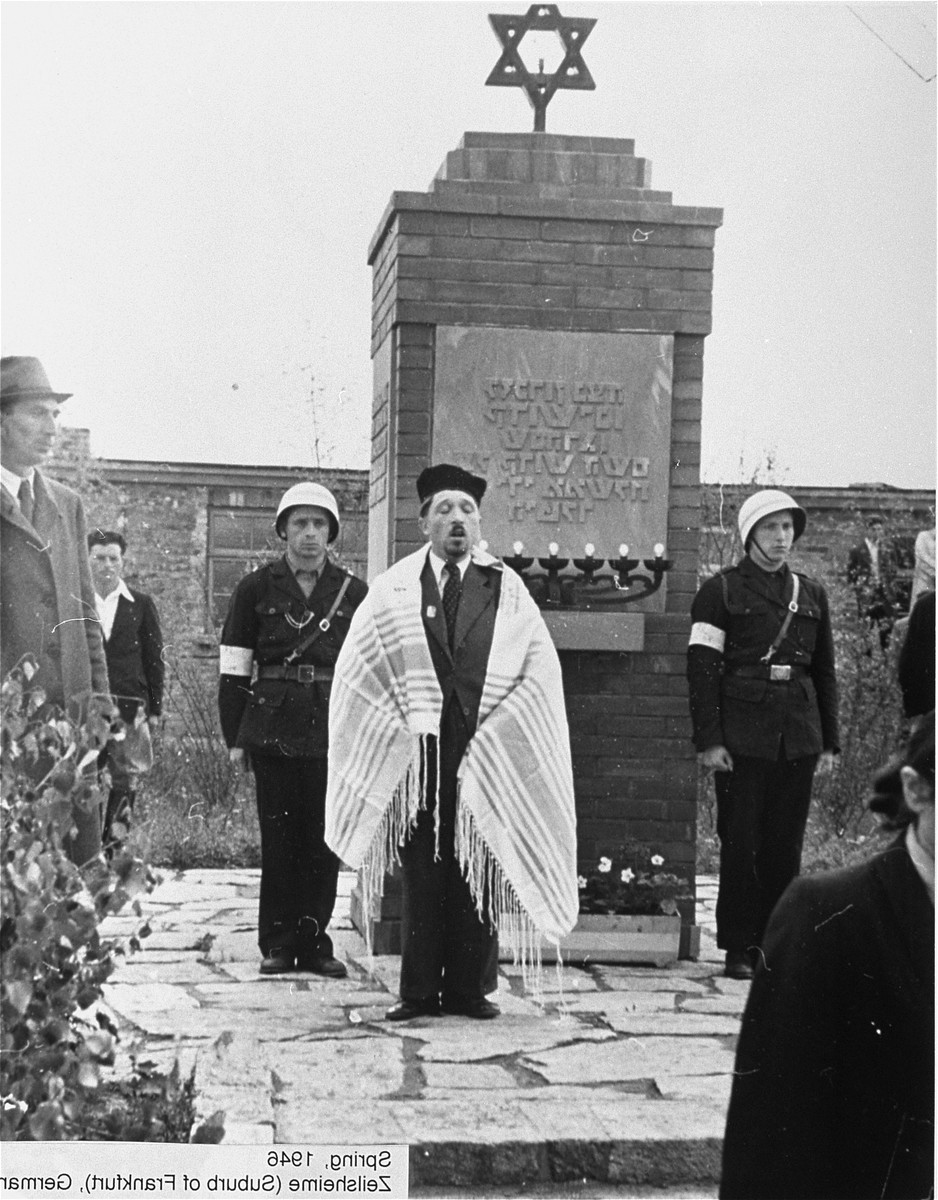 A cantor wearing a prayer shawl recites a prayer in front of a new monument erected at the Zeilsheim displaced persons camp in memory of the Jews killed by the Nazi regime.