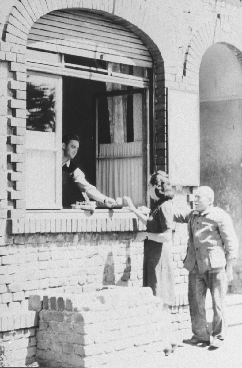 A woman receives food through the window of a building in the Zeilsheim displaced persons' camp.