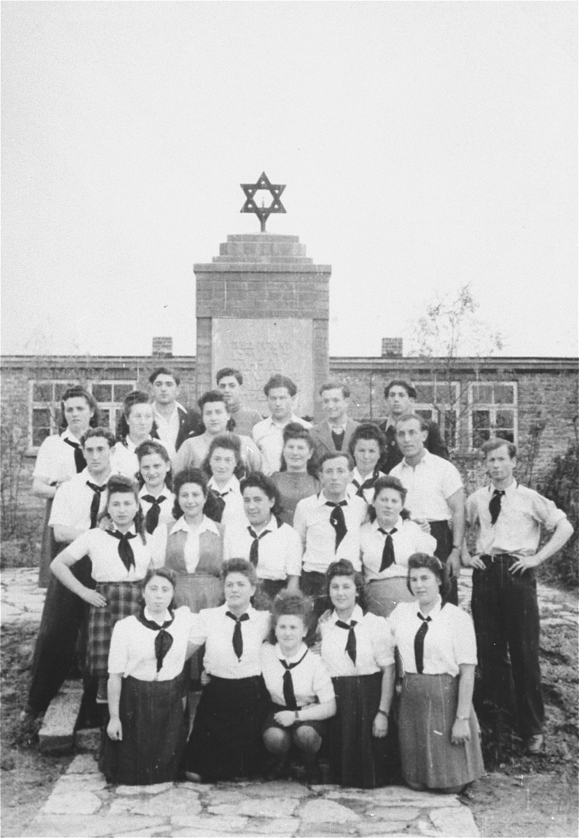 Group portrait of a Zionist youth organization in Zeilsheim standing in front of a memorial to victims of the Holocaust.  Pictured among the group is Sheyne-Bela Berk (Propis).