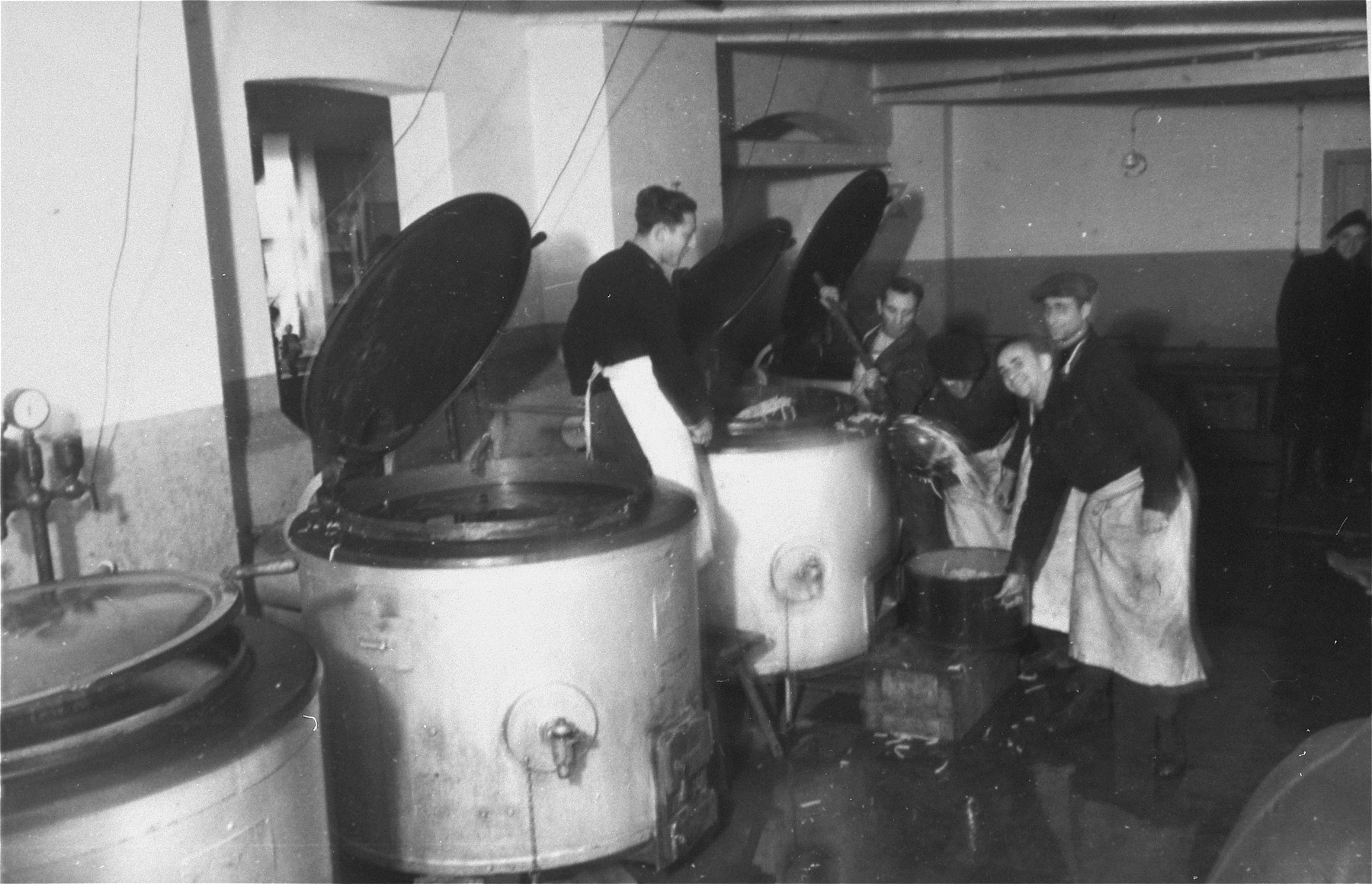 Work in the Zeilsheim camp kitchen pour food from large vats.