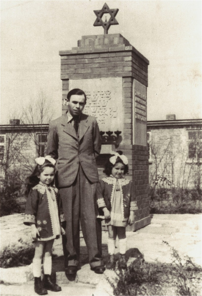 Henia Wisgardisky (left) stands with her father and cousin, Bluma Berk (right), in front of a memorial in the Zeilsheim displaced persons camp.