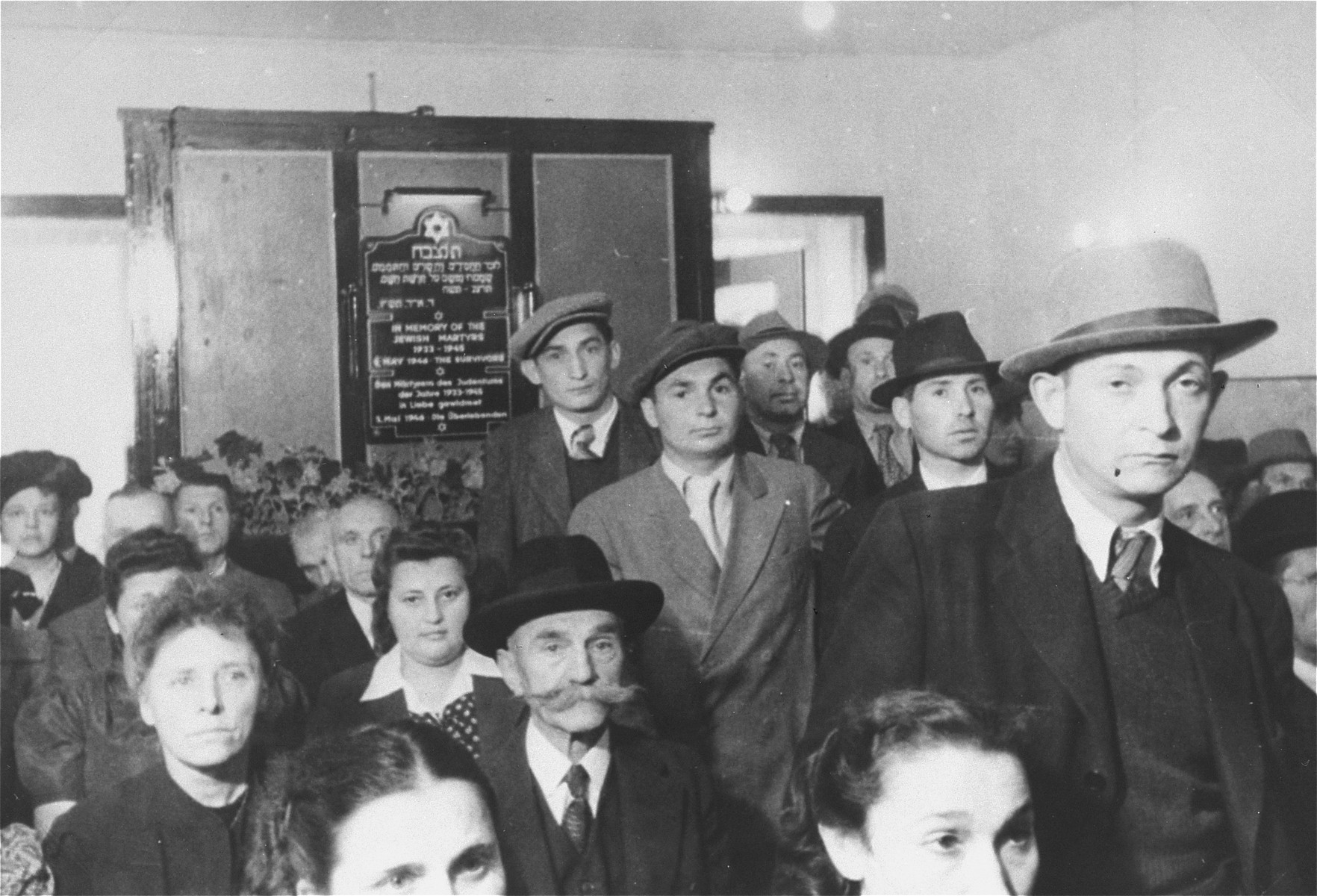 "Jewish displaced persons gather for prayers before a newly installed memorial plaque in the chapel at the Zeilsheim DP camp.    The plaque is written in Hebrew, English and German, and reads "" In Memory of the Jewish Martyrs 1933-1945. 5th May - The Survivors"""