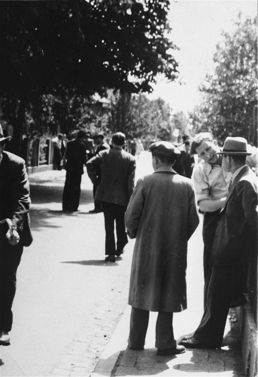 Jewish men walk down a street in the Zeilsheim displaced persons' camp.