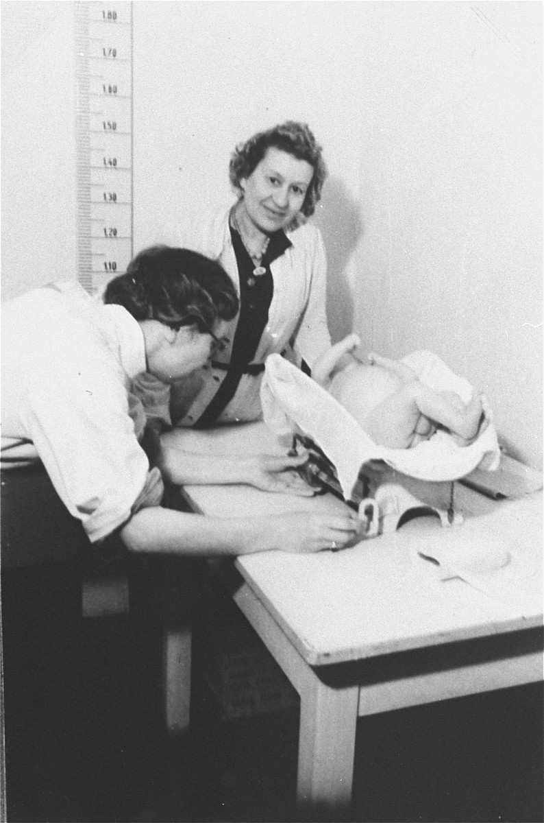 A nurse weighs and measures a young infant in the Zeilsheim displaced person's camp hospital.