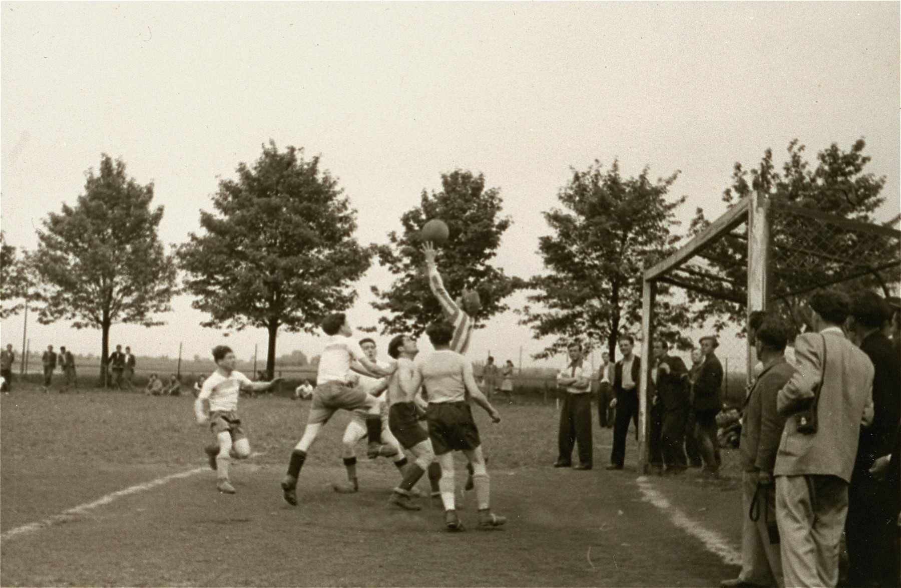 Spectators watch a goalie block a goal during a soccer match at the Zeilsheim displaced persons' camp.