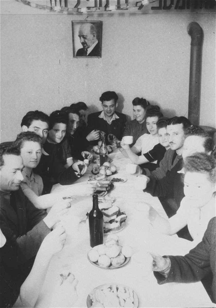 Members of a Zionist youth group in Zeilsheim gather for a celebration around a table laden with food and beverages.