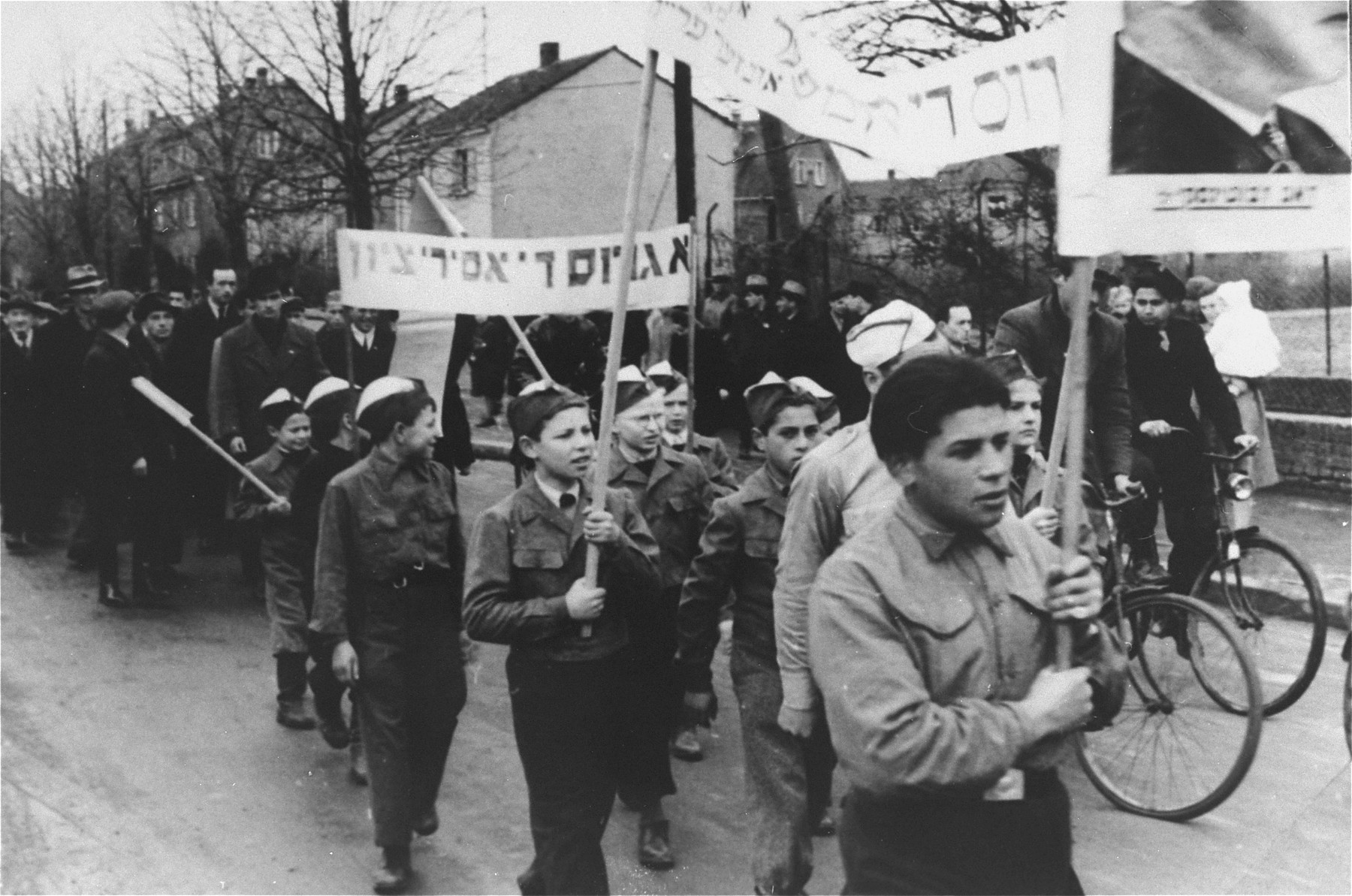 Children in the Zeilsheim displaced persons' camp carrying banners march in a demonstration for free immigration to Palestine.