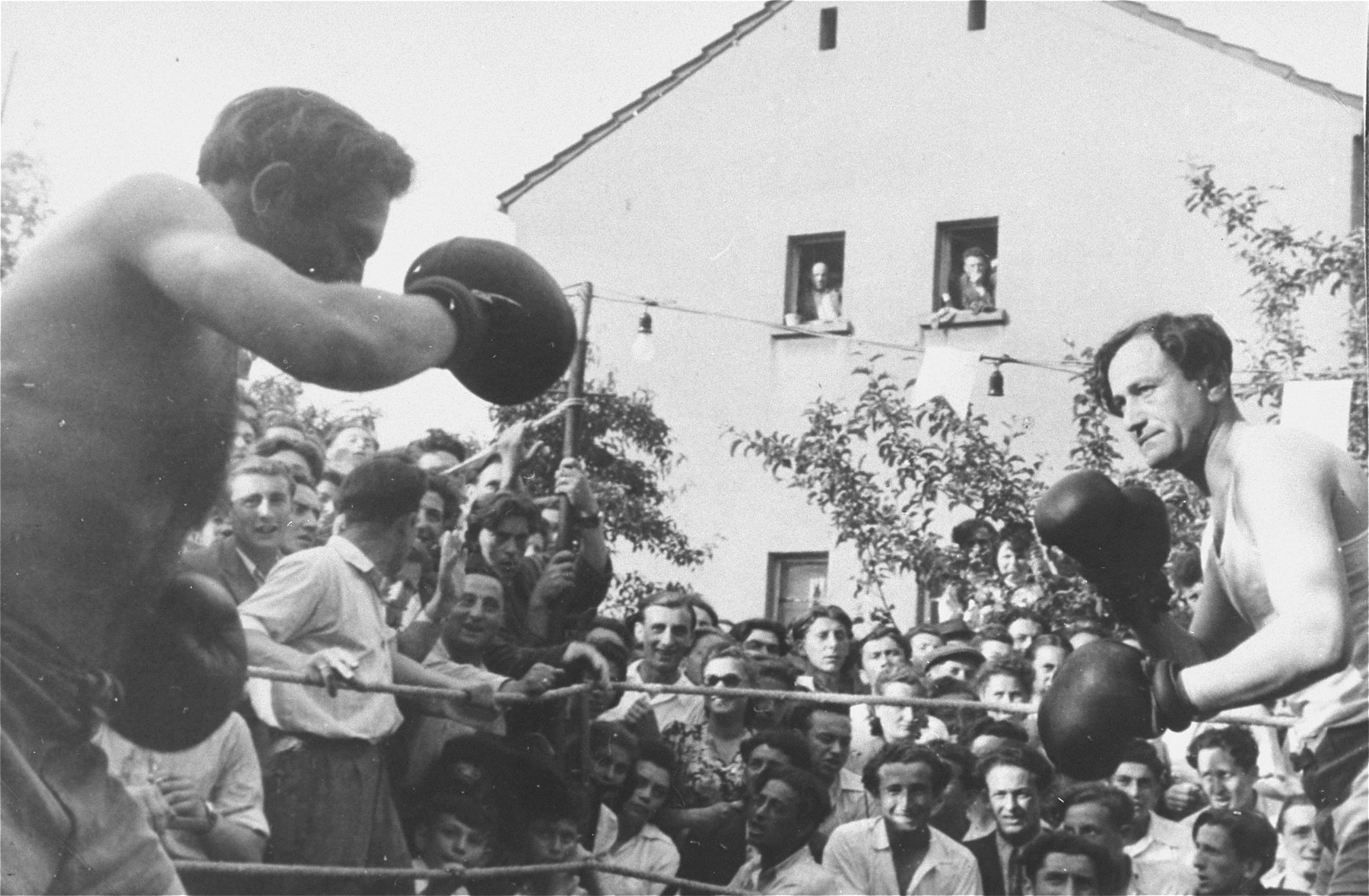 Two boxers spar in the ring during a sports event at the Zeilsheim displaced persons' camp.