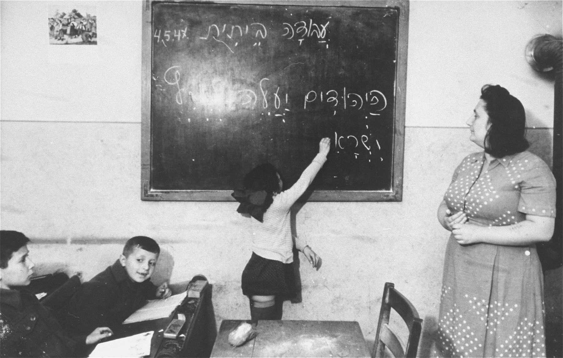"A young girl writes on the blackboard of a Hebrew class in the Zeilsheim displaced person's camp, ""The Jews will immigrate to the Land of Israel""."