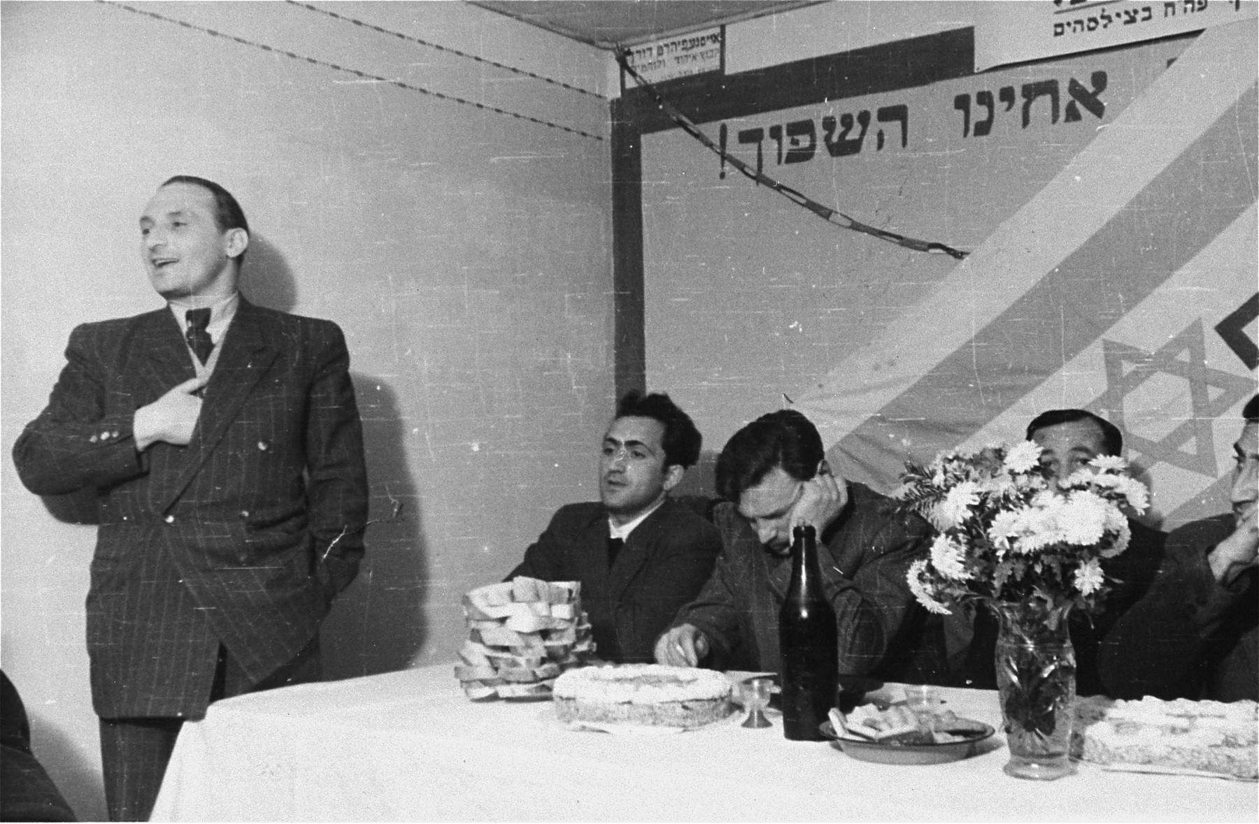 Zionist political meeting in the Zeilsheim displaced person's camp.  Seated third from the left looking down is Yitzhak Zuckerman.