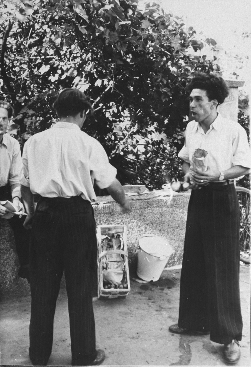 Two men engage in conversation in an outdoor market in the Zeilsheim displaced persons' camp.