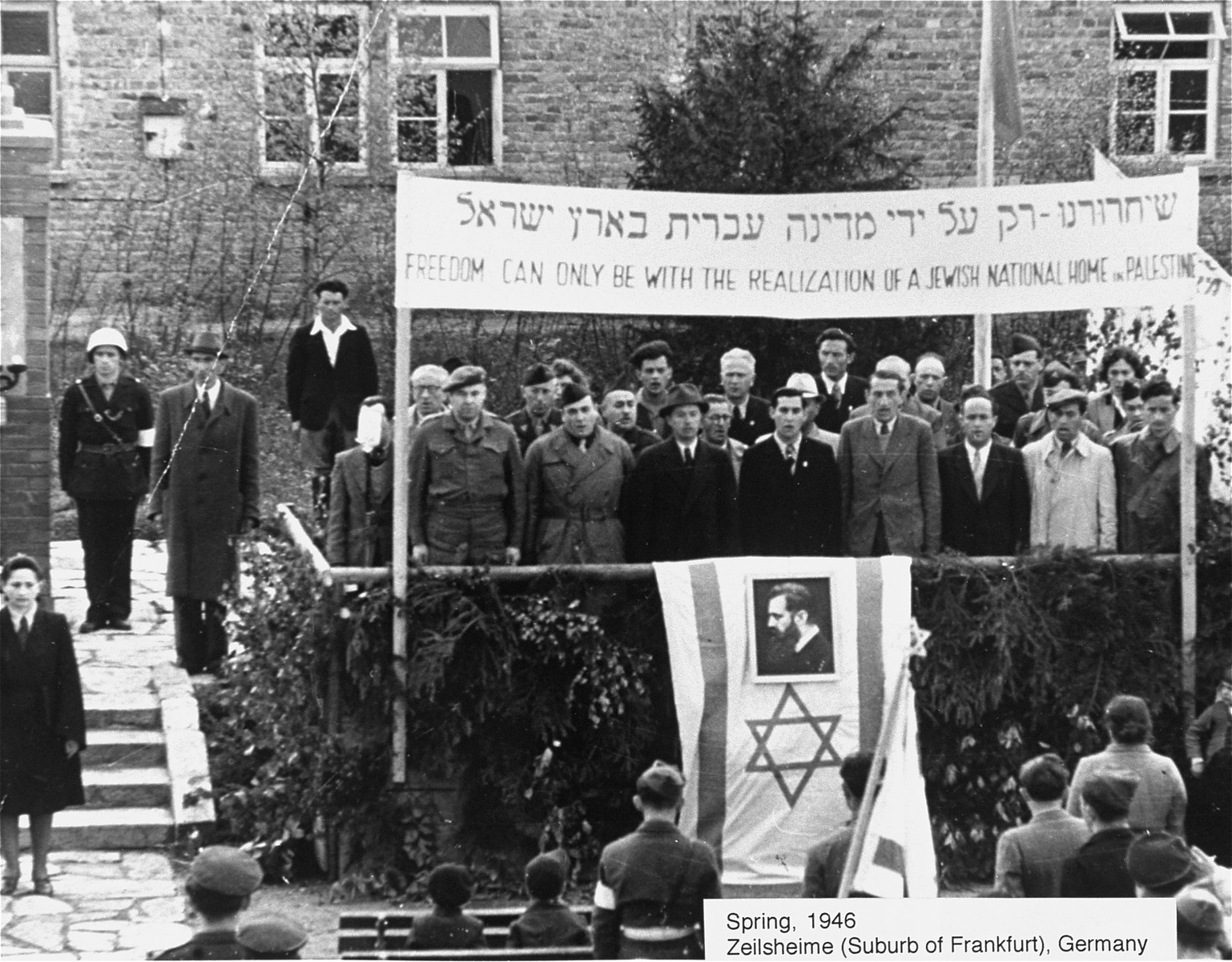 Camp administrators and Zionist leaders, standing beneath a large banner, sing  the Jewish national anthem (Hatikva) at a Zionist rally at the Zeilsheim displaced persons camp.