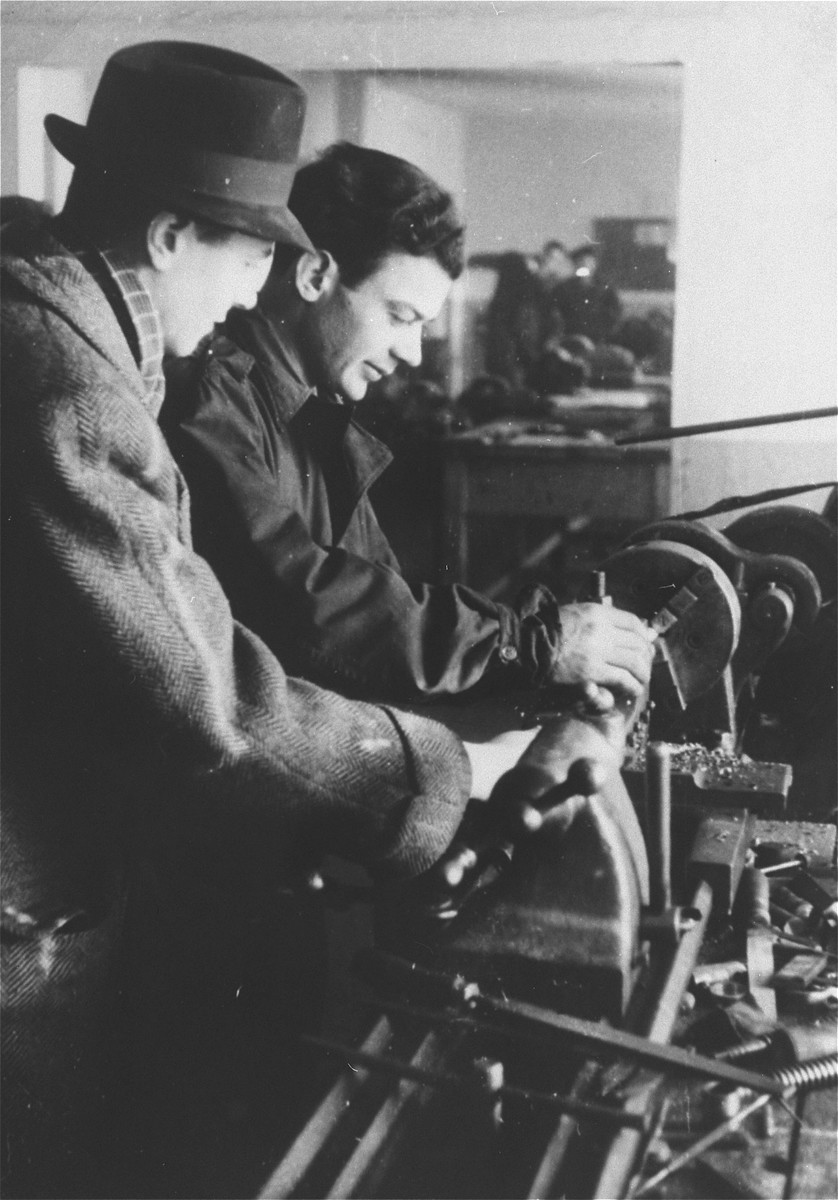 Two men work with a large machine in an ORT vocational school in the Zeilsheim displaced persons' camp.