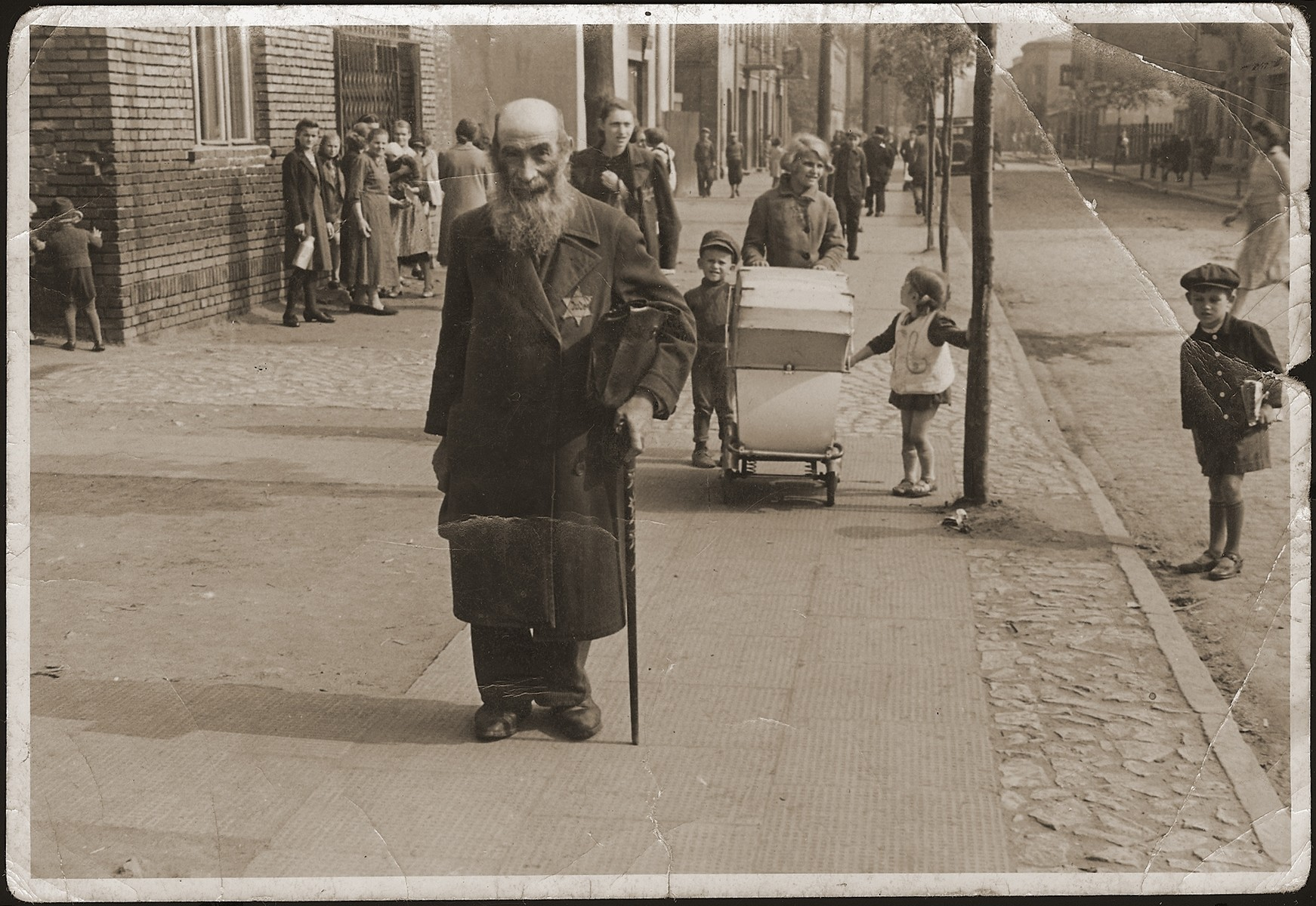 A elderly Polish Jew wearing a Jewish badge, walks along a street in Dabrowa Gornicza.  [Presumably, he has removed his hat in forced deference to the German who is taking his picture.]
