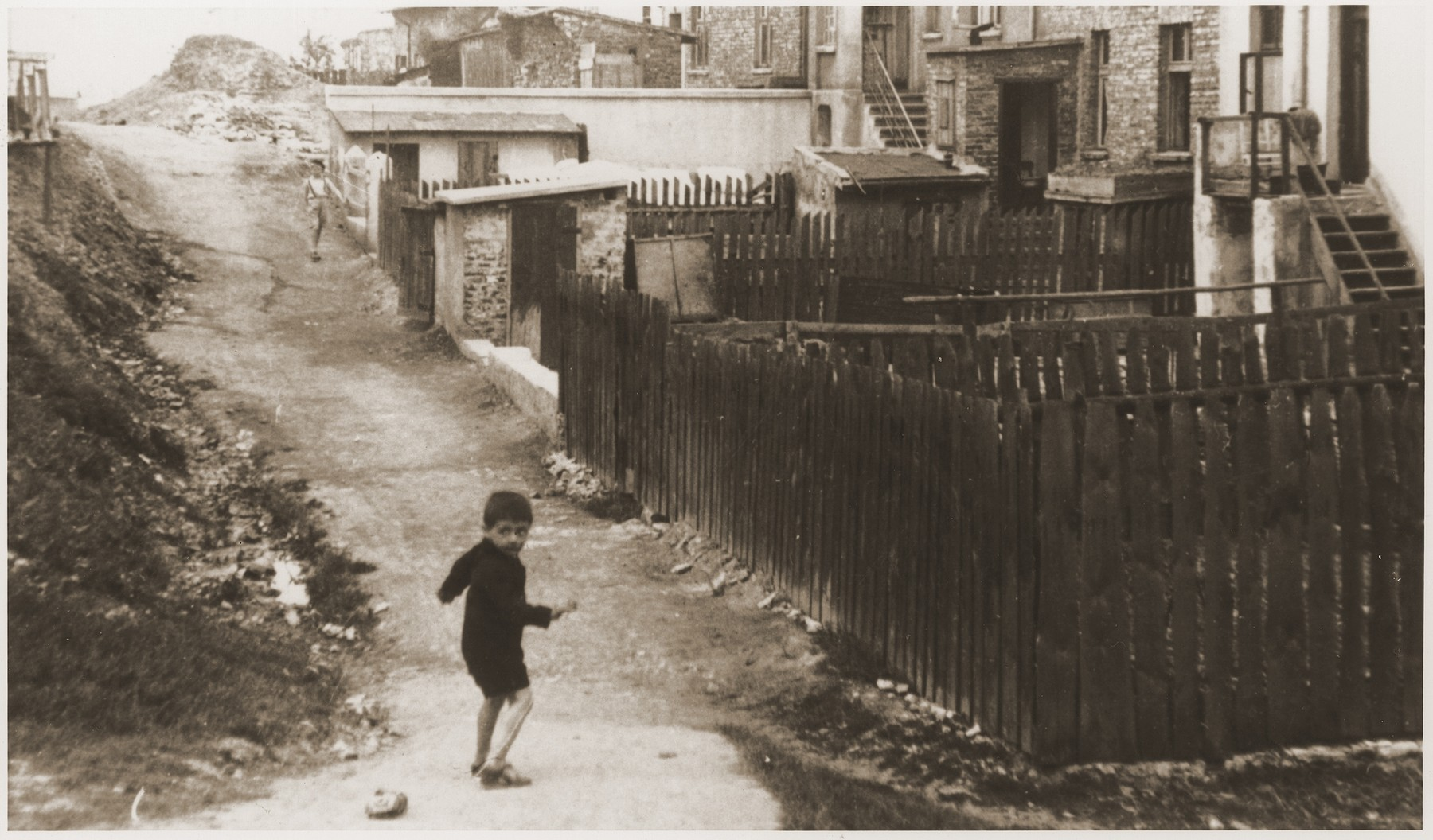 A Jewish boy walking in the back alley in the Bedzin ghetto.