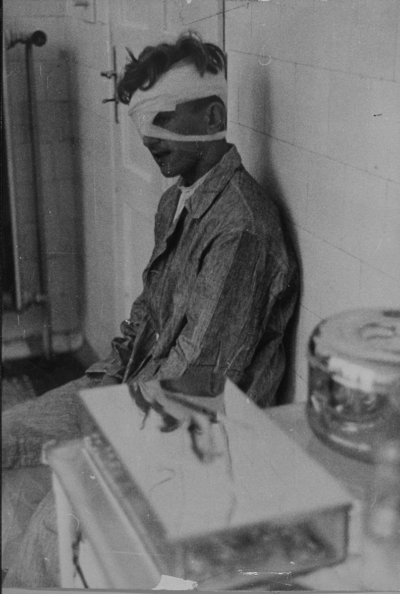 A young man with a bandaged head awaits treatment in an infirmary.