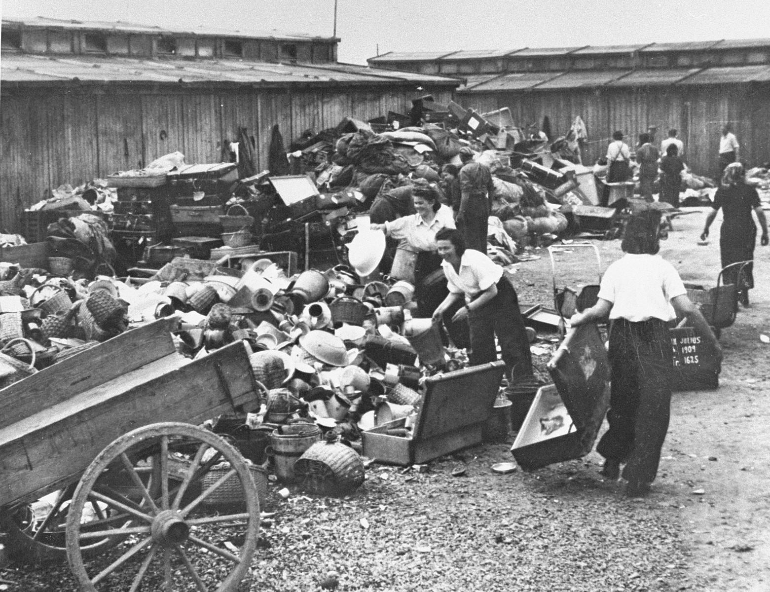 """Prisoners in the Aufräumungskommando (order commandos) unload and sort the confiscated property of a transport of Jews from Subcarpathian Rus at a warehouse in Auschwitz-Birkenau.  The camp prisoners came to refer to the looted property as """"Kanada,"""" associating it with the riches symbolized by Kanada.  The members of this commando were almost exclusively Jews.  """"Kanada"""" storage facilities occupied several dozen barracks and other buildings around the camp.  The looted property was funneled from Auschwitz through an extensive distribution network that served many individuals and various economic branches of the Third Reich."""