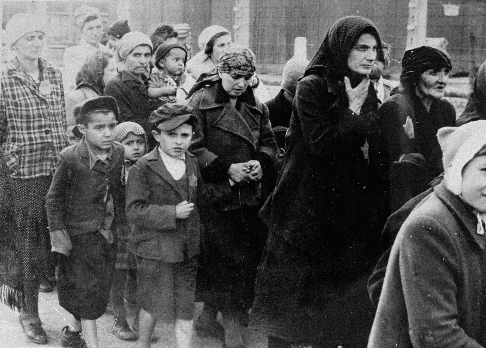 Jewish women and children from Subcarpathian Rus who have been selected for death at Auschwitz-Birkenau, walk toward the gas chambers.  Those pictured include Jolan Wollstein of Szombathely, her children Erwin, Judith, Dori and Naomi, her non-Jewish governess Edith, Henchu Mueller Falkovics, Kreindel Vogel and her sister Sase Vogel and Rita Gruenglass.