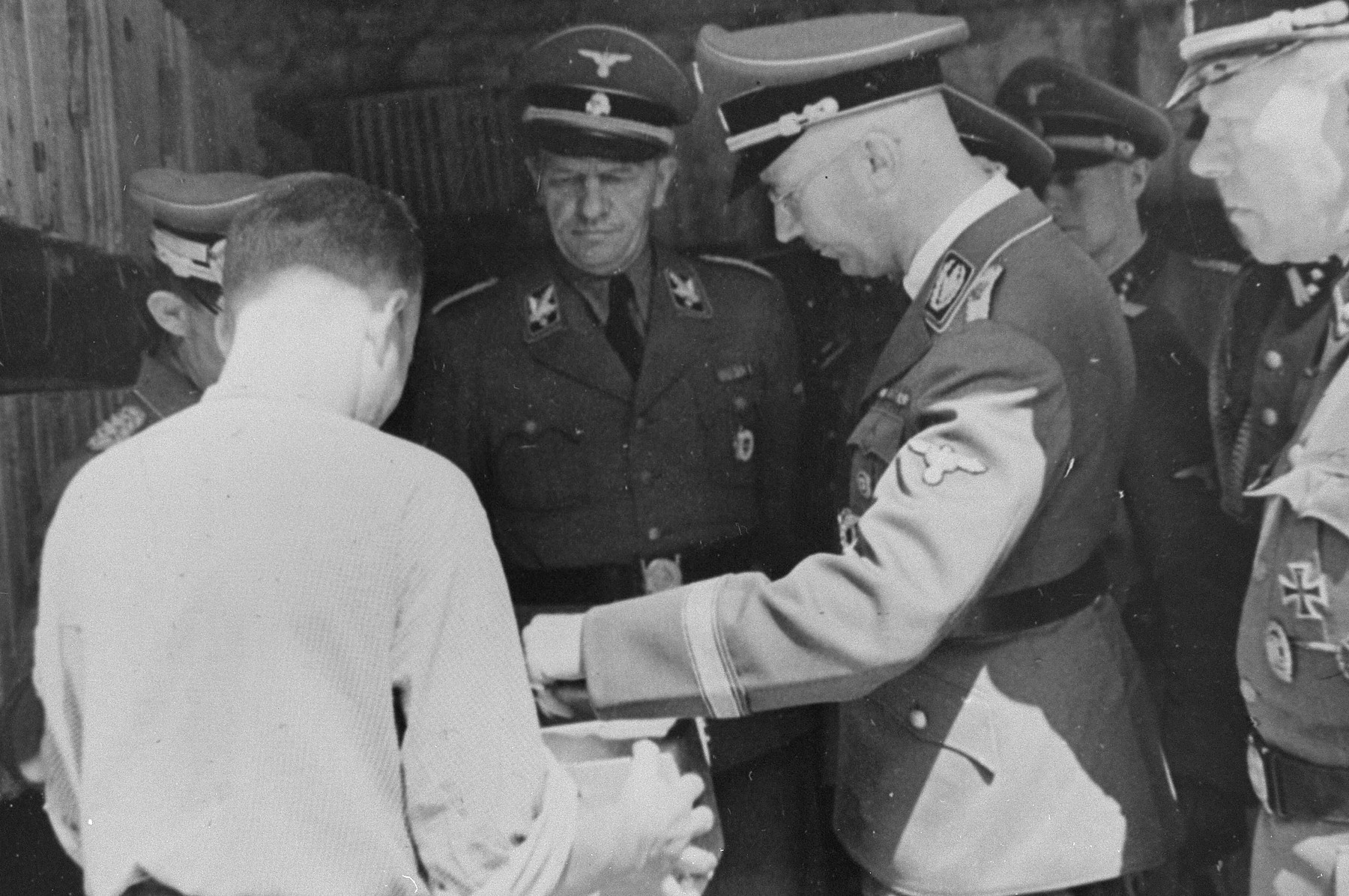 Reichsfuehrer SS Heinrich Himmler examines the contents of a box during an inspection tour of the Monowitz-Buna building site.     Pictured on the far right is Himmler's bodyguard, SS Hauptsturmfuehrer Josef Kiermaier.  In the center is SS-Gruppenfuehrer Hanns Johst.