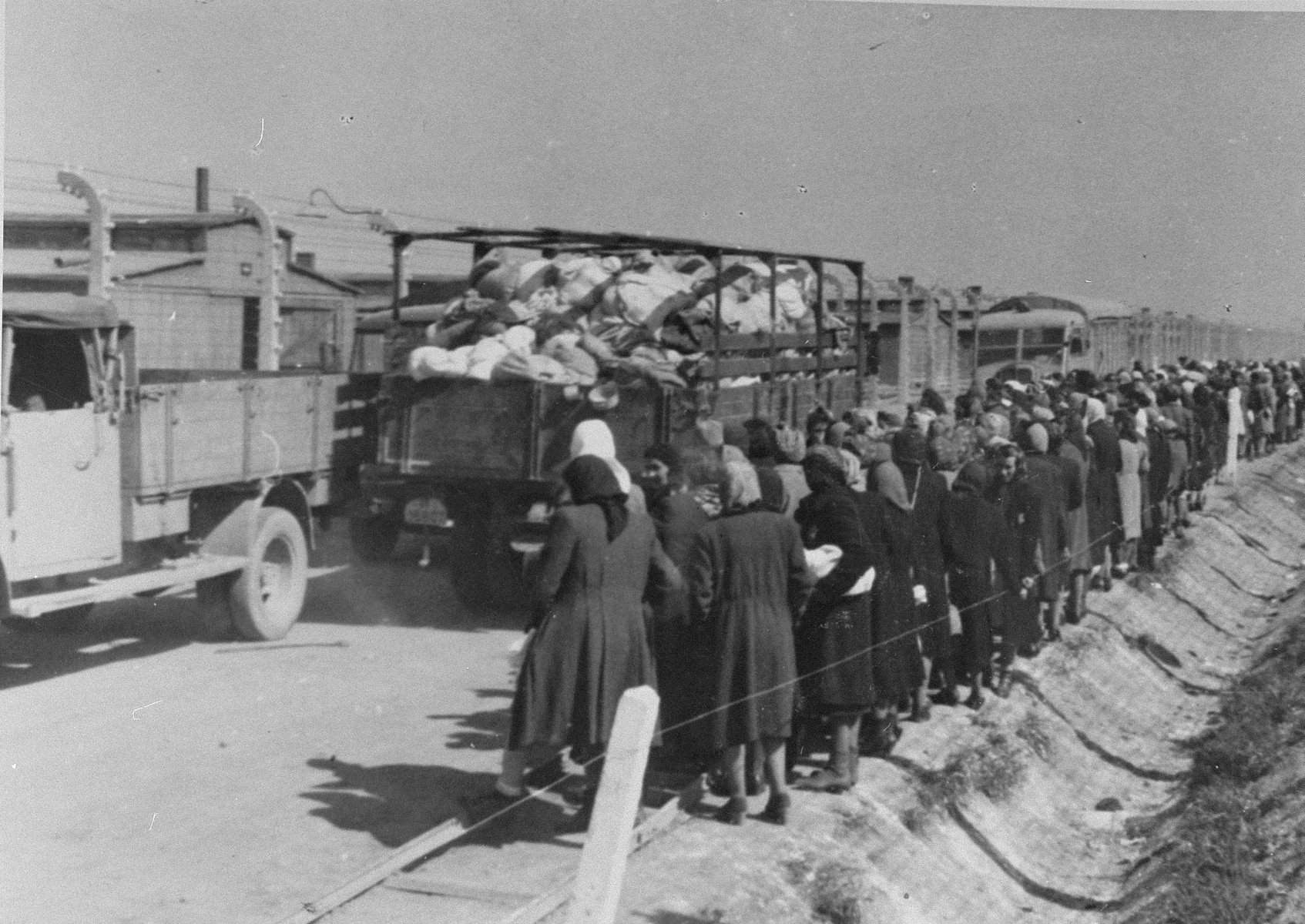 "Jewish women and children from Subcarpathian Rus who have been selected for death, watch as trucks loaded with confiscated personal property drive past on their way to the ""Kanada"" warehouses.   The camp prisoners came to refer to the looted property as ""Kanada,"" associating it with the riches symbolized by Kanada.  The members of this commando were almost exclusively Jews.  ""Kanada"" storage facilities occupied several dozen barracks and other buildings around the camp.  The looted property was funneled from Auschwitz through an extensive distribution network that served many individuals and various economic branches of the Third Reich."