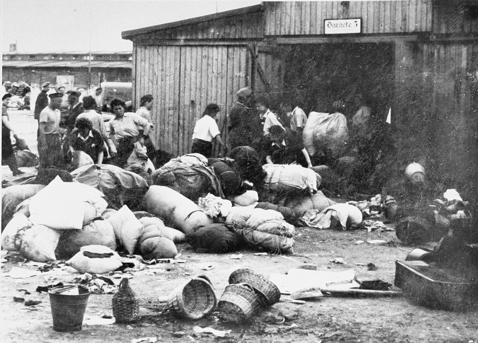 """Prisoners in the Aufräumungskommando (order commandos) move the confiscated property of a transport of Jews from Subcarpathian Rus into a warehouse in Auschwitz-Birkenau.  The camp prisoners came to refer to the looted property as """"Kanada,"""" associating it with the riches symbolized by Kanada.  The members of this commando were almost exclusively Jews.  """"Kanada"""" storage facilities occupied several dozen barracks and other buildings around the camp.  The looted property was funneled from Auschwitz through an extensive distribution network that served many individuals and various economic branches of the Third Reich."""