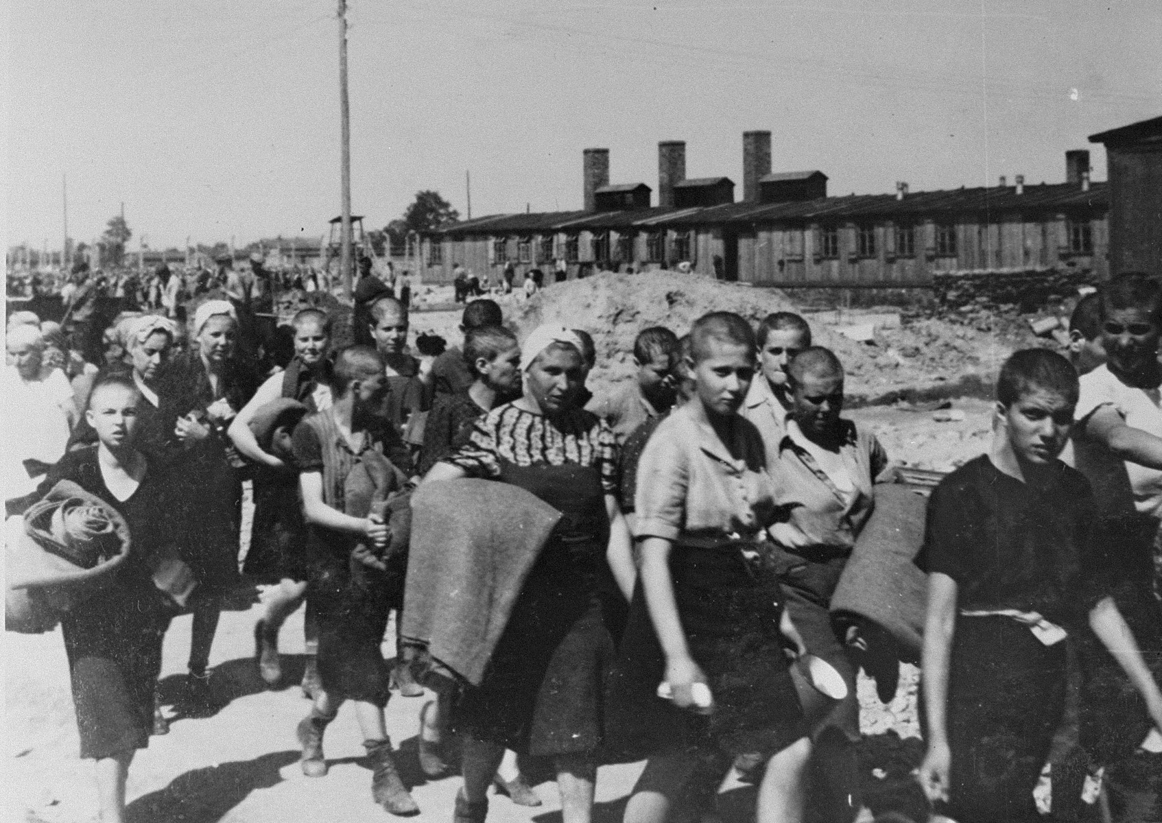 Jewish women from Subcarpathian Rus who have been selected for forced labor at Auschwitz-Birkenau, march toward their barracks carrying bed rolls after disinfection and headshaving.