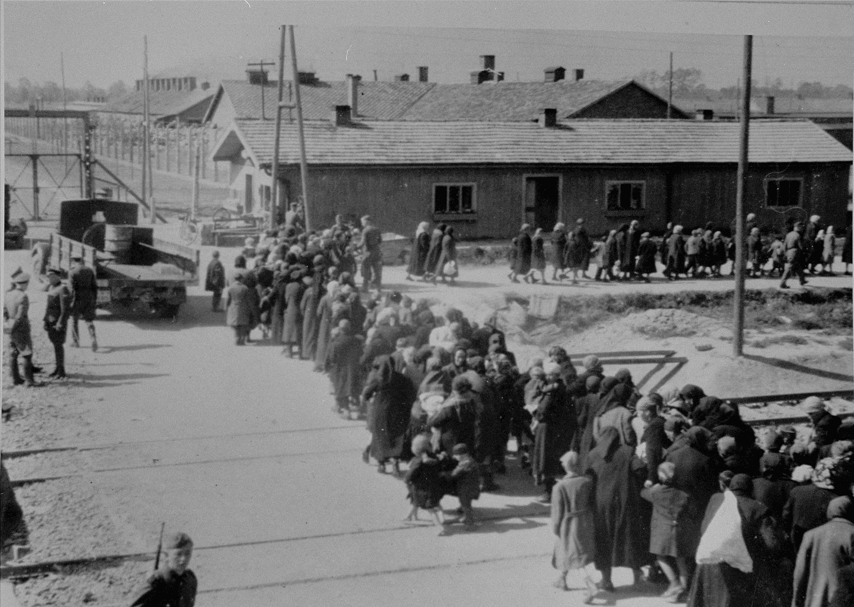 Jewish women and children who have been selected for death, walk in a line towards the gas chambers.   The gate at the upper left  leads to the section of the camp on the south side of the ramp known as BI.