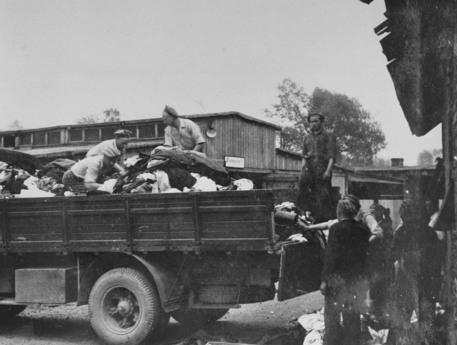 """Prisoners in the Aufräumungskommando (order commandos) unload the confiscated property of a transport of Jews from Subcarpathian Rus at a warehouse in Auschwitz-Birkenau.  The camp prisoners came to refer to the looted property as """"Kanada,"""" associating it with the riches symbolized by Kanada.  The members of this commando were almost exclusively Jews.  """"Kanada"""" storage facilities occupied several dozen barracks and other buildings around the camp.  The looted property was funneled from Auschwitz through an extensive distribution network that served many individuals and various economic branches of the Third Reich."""