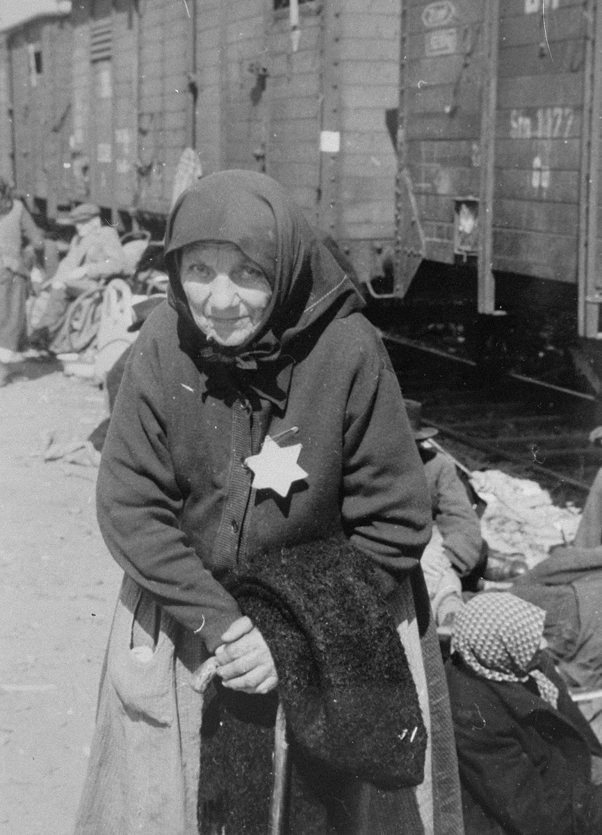 Perla Schwartz, an elderly Jewish woman from Subcarpathian Rus who has been selected for death, waits on the ramp at Auschwitz-Birkenau to be taken to the gas chambers.