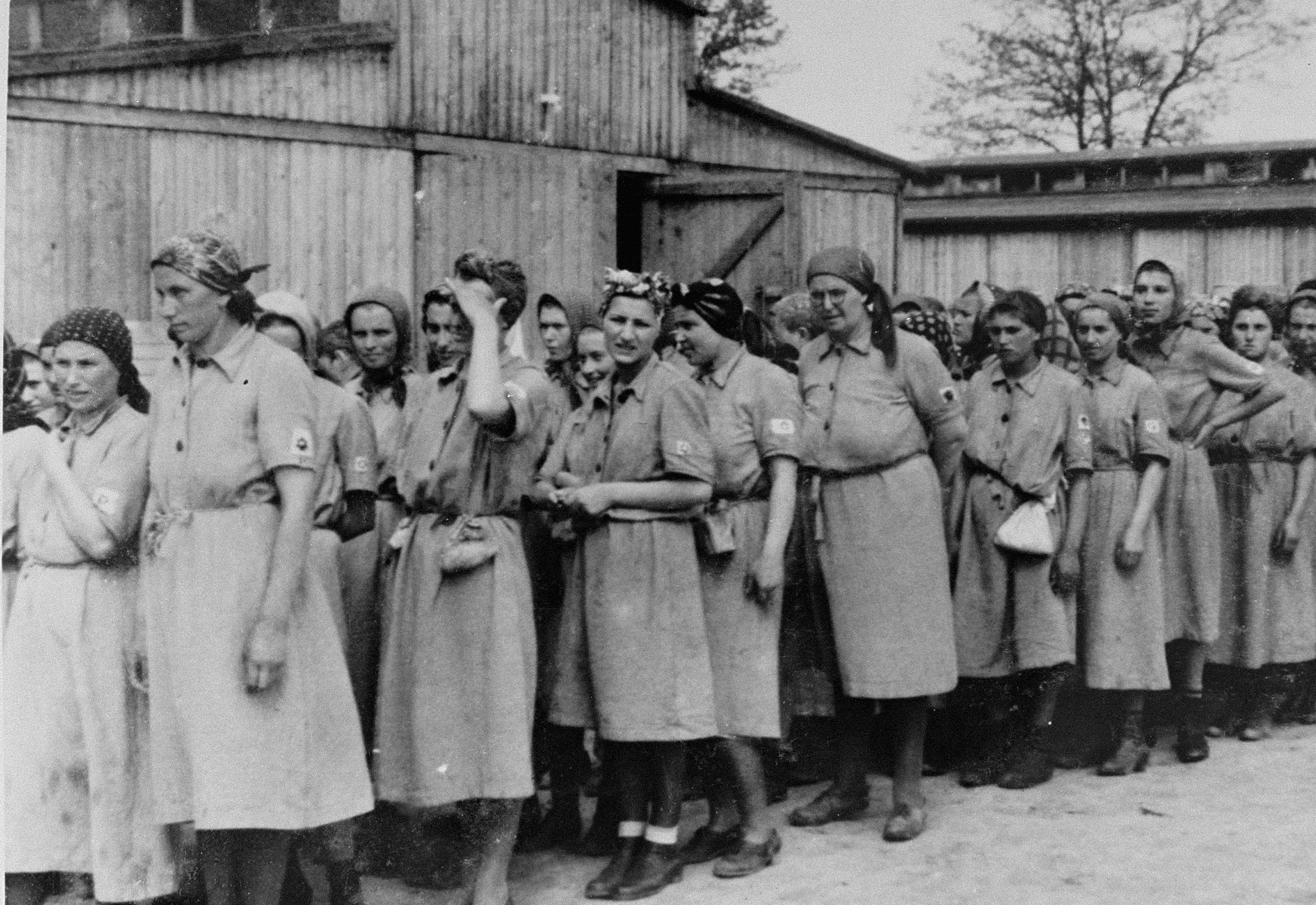 Jewish women from Subcarpathian Rus who have been selected for forced labor at Auschwitz-Birkenau, march toward their barracks after disinfection and headshaving.  Those pictured include Olga Rieder and her sister, Rozi Feldman, Suri Birnbaum, Fradi Birnbaum, Cilli Hochmann, Maidi Birnbaum, and Piri Birnbaum.  The Birnbaum sisters were singers who occassionally performed for the Germans in the camp.