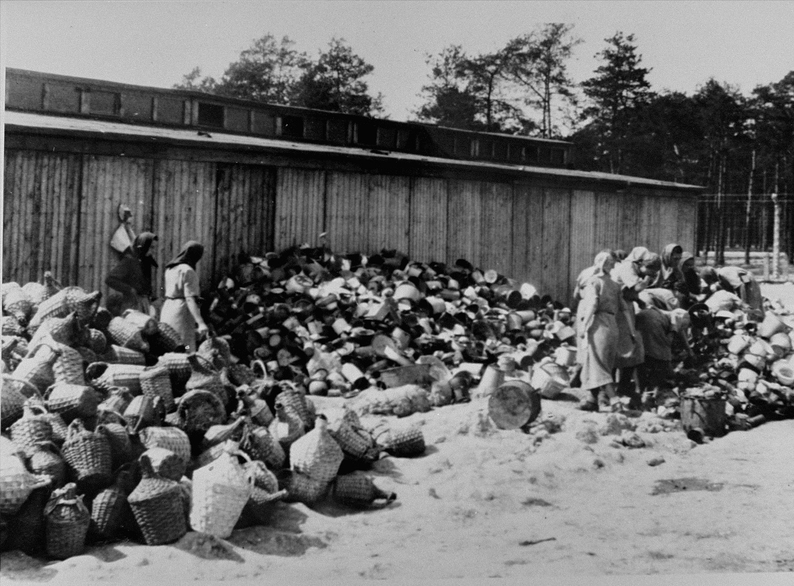 """Female prisoners in the Aufräumungskommando (order commandos) sort the confiscated property of a transport of Jews from Subcarpathian Rus at a warehouse in Auschwitz-Birkenau.  The camp prisoners came to refer to the looted property as """"Kanada,"""" associating it with the riches symbolized by Kanada.  The members of this commando were almost exclusively Jews.  """"Kanada"""" storage facilities occupied several dozen barracks and other buildings around the camp.  The looted property was funneled from Auschwitz through an extensive distribution network that served many individuals and various economic branches of the Third Reich."""