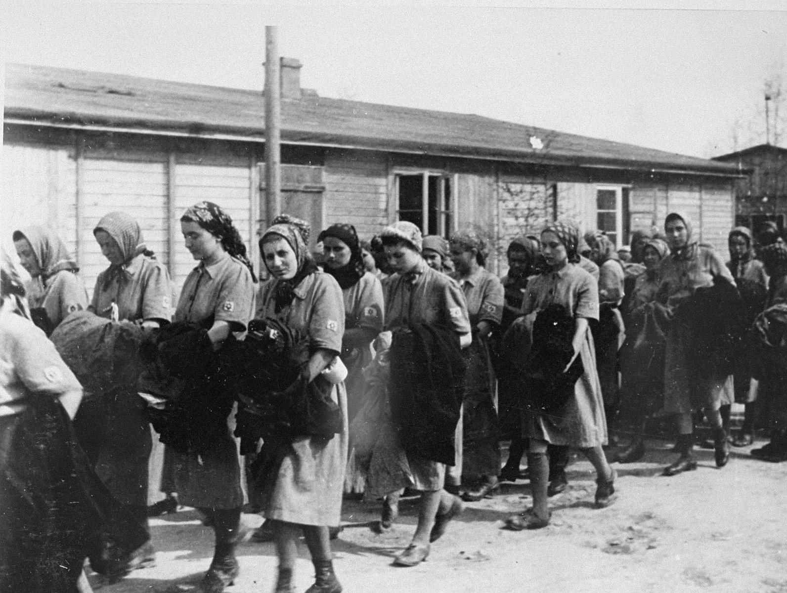 Jewish women from Subcarpathian Rus who have been selected for forced labor at Auschwitz-Birkenau, march toward their barracks after disinfection and headshaving.  Among those pictured from left to right are Martha Birnbaum Younger, Dora Birnbaum, Erna Birnbaum Gottesman, Gina Liebermann or Etush Zelmanovic (later Esther Moses),  Agi Katz Rubin, and Mignon Gottesman (now Bretzholz), Maidi Birnbaum and Rozi Feldman.