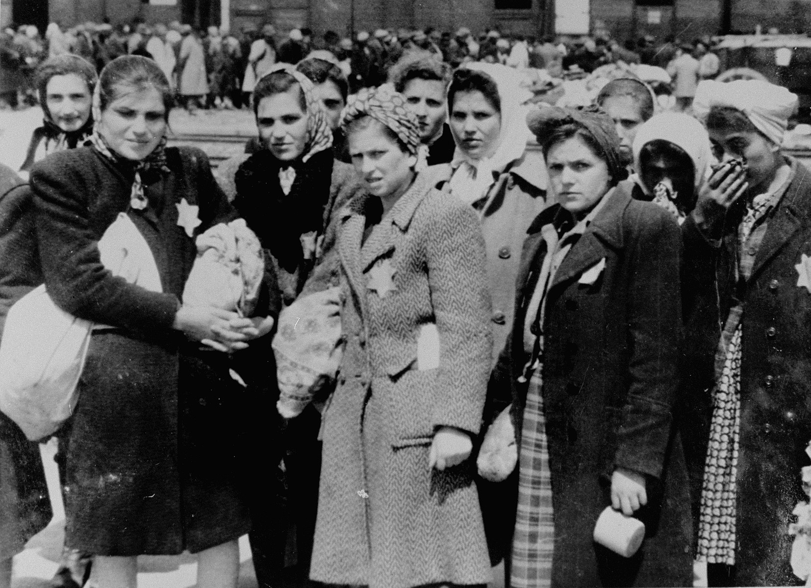 Jewish women from Subcarpathian Rus who have been selected for forced labor at Auschwitz-Birkenau, wait to be taken to another section of the camp.  Pictured from left to right are Lili (Mueller) Yakobovics, Sima Mueller and Rozi (Mueller) Bittman, three sisters from Tesco.  Rozi (Smilovics) Grever is standing second from right, holding a cup. Her sisters Mariska (Smilovics) Mueller and Gitza are in the center in the second row.  Also pictured are Ester Klein (far left, back row), and Elly Berkovits, center back with her cheek and mouth partially obscured (see her mother and brother in photogaph #77295).  Also possibly pictured are Rifcsu and Leah Dressler.