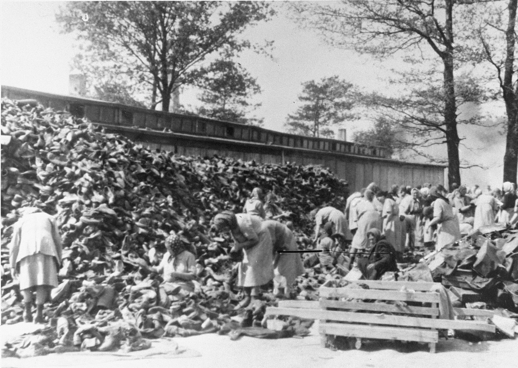 "Auschwitz women inmates sort through a huge pile of shoes from the transport of Hungarian Jews.   Female prisoners in the Aufräumungskommando (order commandos) sort through a pile of shoes confiscated from a transport of Jews from Carpathian Ruthenia at a warehouse in Auschwitz-Birkenau.  The camp prisoners came to refer to the looted property as ""Kanada,"" associating it with the riches symbolized by Kanada.  The members of this commando were almost exclusively Jews.  ""Kanada"" storage facilities occupied several dozen barracks and other buildings around the camp.  The looted property was funneled from Auschwitz through an extensive distribution network that served many individuals and various economic branches of the Third Reich."