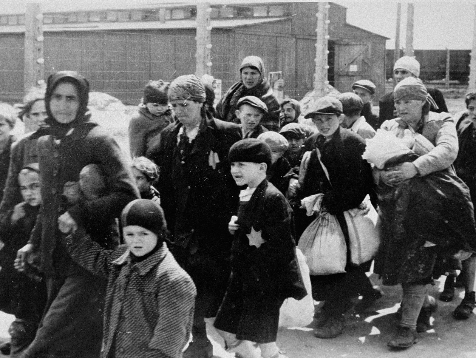 Jewish women and children from Subcarpathian Rus who have been selected for death at Auschwitz-Birkenau, walk toward the gas chambers.  Bracha Junger is pictured on the far left holding the hands of her two children.