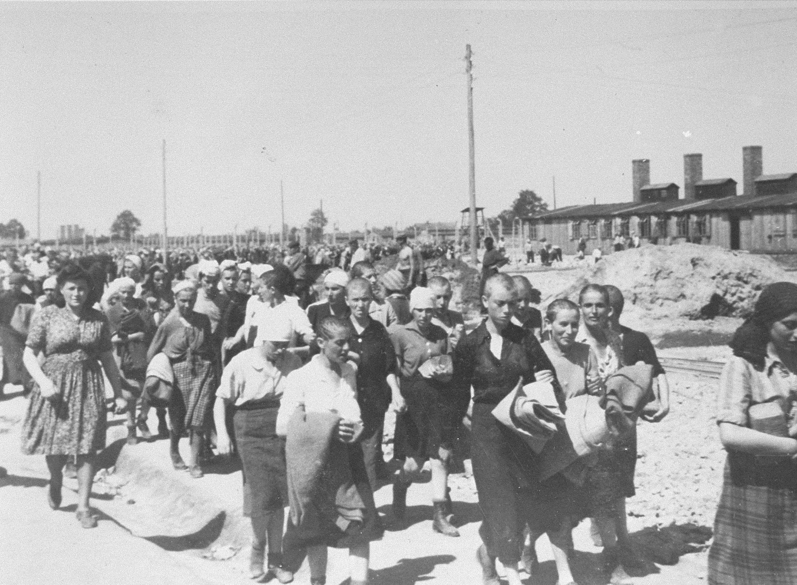 Jewish women from Subcarpathian Rus who have been selected for forced labor at Auschwitz-Birkenau, march toward their barracks after disinfection and headshaving.    The woman on the left with a full head of hair is the Blockaelteste.  The building on the right is the kitchen of the women's camp.  Pictured in the back is Hildegard Taussig.