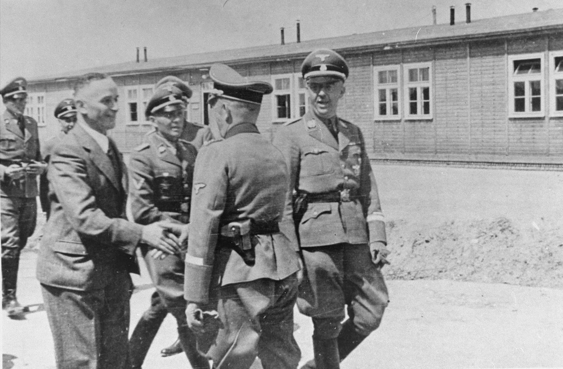 Officials at the Monowitz-Buna building site greet Reichsfuehrer SS Heinrich Himmler and his inspection team.     Among those pictured are Max Faust (left, wearing a suit), the manager of building operations for IG Farben in Monowitz-Buna; Auschwitz commandant Rudolph Hoess (second from the left, next to Faust); SS Obergruppenfuehrer Ernst Schmauser (shaking hands with Faust), and SS-Reichsfuehrer Heinrich Himmler (far right).
