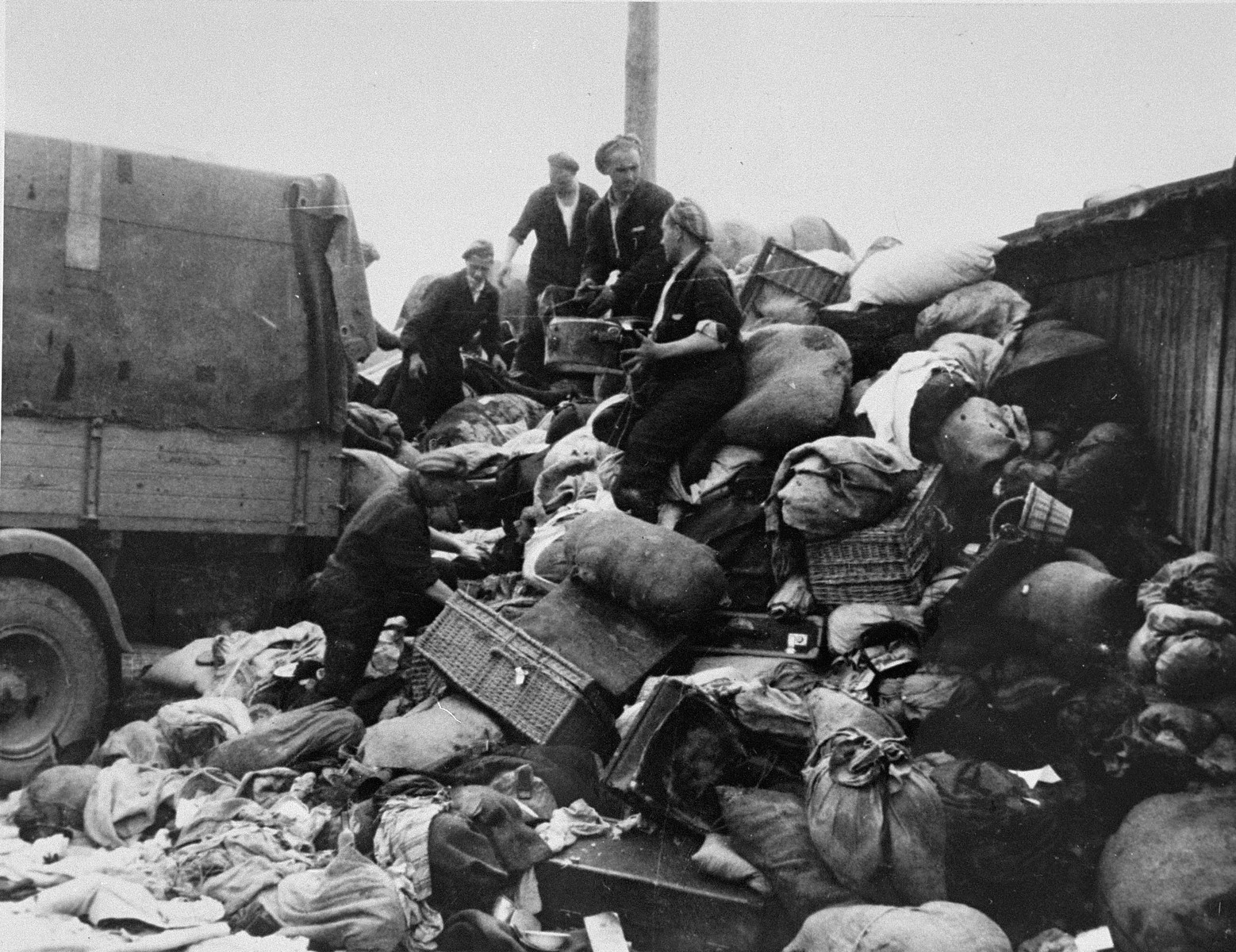"""Prisoners in the Aufräumungskommando (order commandos) unload the confiscated property of a transport of Jews from Subcarpathian Rus at a warehouse in Auschwitz-Birkenau.  Matyi (later Martin Kuban) Klein is pictured in the center.  Originally from Secovice, Czechoslovakia, Klein was reponsible for the horse and wagons used to transport prisoner belongings.  According to his family, he transported dynamite hidden in the axel of one of the wagons prior to the Auschwitz uprising.  The camp prisoners came to refer to the looted property as """"Kanada,"""" associating it with the riches symbolized by Kanada.  The members of this commando were almost exclusively Jews.  """"Kanada"""" storage facilities occupied several dozen barracks and other buildings around the camp.  The looted property was funneled from Auschwitz through an extensive distribution network that served many individuals and various economic branches of the Third Reich."""