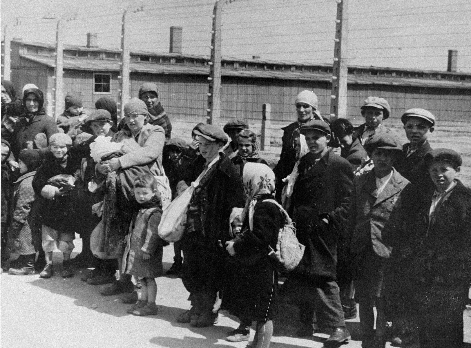 Jewish women and children from Subcarpathian Rus who have been selected for death at Auschwitz-Birkenau, wait to be taken to the gas chambers.   Bracha Junger is standing on the left.